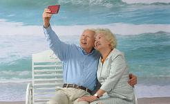 casal mais velho de cabelos brancos sentado em um banco na praia tirando uma selfie
