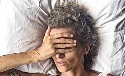 امرأة مستلقية على وسادة بيضاء تضع يدها على وجهها