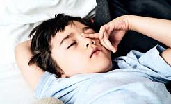 Un jeune garçon se frotte les yeux alors qu'il est allongé dans son lit