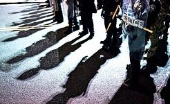 Sederet polisi dengan perisai anti huru hara di jalan membuat bayangan di aspal
