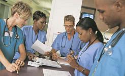 Gruppe von Angehörigen der Gesundheitsberufe, die um einen Schreibtisch oder Tisch herum stehen