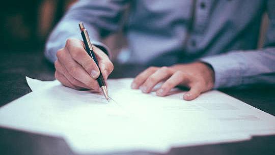 一個男人在紙上寫字的照片