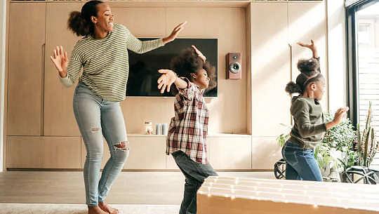 Женщина и дети танцуют счастливо