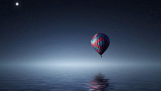 luna llena sobre un globo aerostático