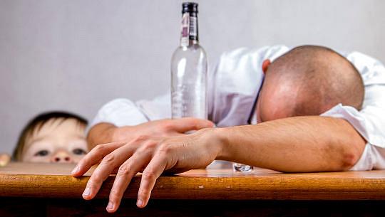 lalaki ay dumaan sa isang mesa na may isang bote ng alkohol na may bata na nakatingin
