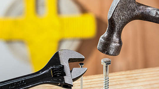 un marteau essayant d'enfoncer un boulon et une clé essayant de travailler sur un clou