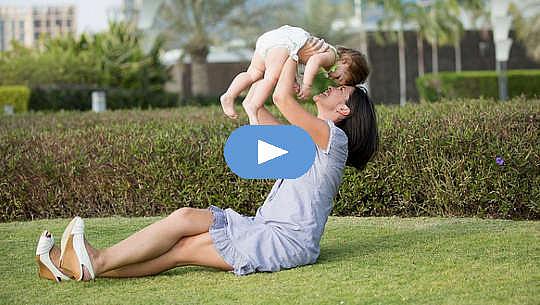 مادر خندان، نشسته روی چمن، کودکی را در آغوش گرفته است