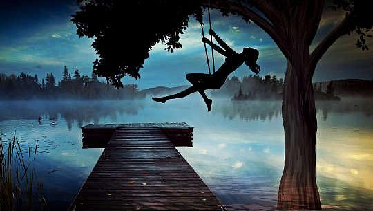 धुंधली झील को देखते हुए शाम के समय झूले पर ऊंची लड़की का सिल्हूट