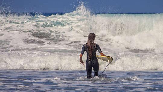 Surfer mit winzigem Surfbrett vor riesigen Wellen