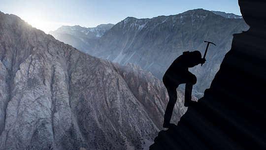 fotosilhouett av bergsklättrare med hjälp av en plockning för att säkra sig