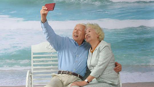 пожилая седая пара сидит на скамейке на пляже и делает селфи