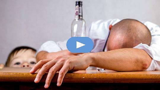 pria pingsan di atas meja dengan sebotol alkohol kosong dengan anak-anak melihat looking
